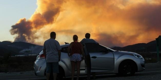 Des gens observent l'incendie de Blue Cut à l'est de Los Angeles, aux Etats-Unis, le 16 août 2016