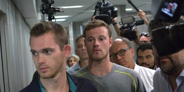 Journalists surround American Olympic swimmers Gunnar Bentz, left, and Jack Conger, center, as they leave the police station at Rio International airport early Thursday Aug. 18, 2016. The two were taken off their flight from Brazil to the U.S. on Wednesday by local authorities amid an investigation into a reported robbery targeting Ryan Lochte and his teammates. According to their lawyer they will not be allowed to leave Brazil until they provide testimony about the robbery. (AP Photo/Mauro Pime