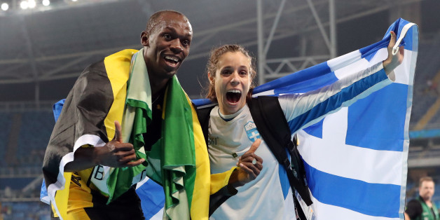 Gold medalist in the men's 4x100-meter relay final Jamaica's Usain Bolt celebrates with gold medalist in the women's pole vault Greece's Ekaterini Stefanidi during the athletics competitions of the 2016 Summer Olympics at the Olympic stadium in Rio de Janeiro, Brazil, Friday, Aug. 19, 2016. (AP Photo/Lee Jin-man)