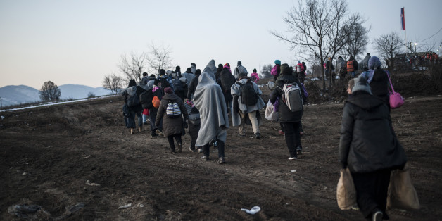 Migrants and refugees with blankets covering their shoulders walk after crossing the Macedonian border into Serbia, near the village of Miratovac, on January 23, 2016