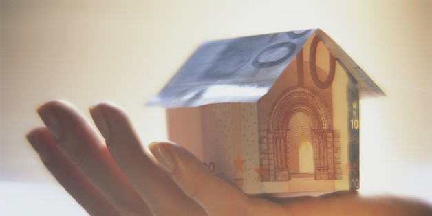 Hand Holding Paper House Made of Euro Notes
