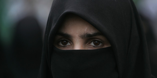 "A supporter of Pakistani religious party Jamaat-i-Islami attends a rally to condemn the ban imposed on the burqa or veil in France, on Tuesday, April 19, 2011 in Karachi, Pakistan. France on Monday April 11, 2011 became the first country to enact a law designed to forbid face-covering veils such as the niqab or burqa anywhere in public. Violators risk fines or citizenship classes. A 2004 law bans Muslim headscarves and other ""ostentatious"" religious symbols from classrooms. (AP Photo/Shakil Adil)"
