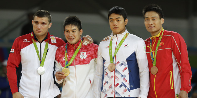 Medal winners in the men's 90 kg judo competition of the 2016 Summer Olympics stand on the podium in Rio de Janeiro, Brazil, Wednesday, Aug. 10, 2016. They are, from left, silver medal winner Varlam Liparteliani of Georgia, gold medal winner Mashu Baker of Japan, and bronze medalists Gwak Dong-han of South Korea and Cheng Xunzhao of China. (AP Photo/Gregory Bull)