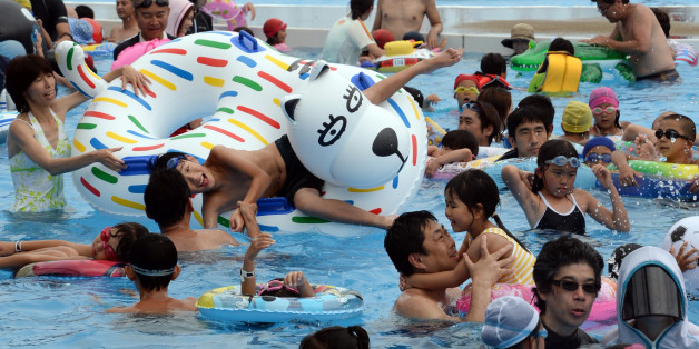 Visitors beat the summer heat at the Yomiuri Land Water Amusement Island (WAI) in Tokyo on July 14, 2013. More than 10,000 visitors enjoy the hot summer weekend at the swimming pools as the temperatures approached 35 degrees celsius in Tokyo.      AFP PHOTO / TOSHIFUMI KITAMURA        (Photo credit should read TOSHIFUMI KITAMURA/AFP/Getty Images)