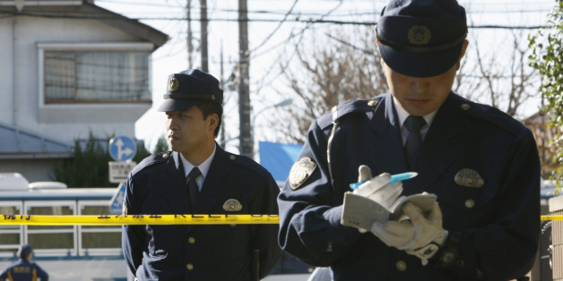 Policemen stand guard at a police line near the house where the wife of a former vice health minister was stabbed, in Tokyo November 19, 2008. The suspected murder of a former vice health minister and the stabbing of the wife of another, both with careers tied to Japan's ailing pension system, prompted Japanese police to tighten security for officials on Wednesday.   REUTERS/Kim Kyung-Hoon (JAPAN)