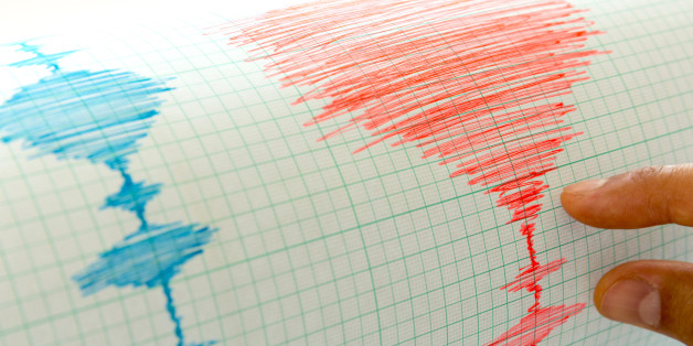 Seismological device for measuring earthquakes. Seismological activity live on the sheet of measuring paper. Earthquake wave on graph paper. Human hand showing earthquake.