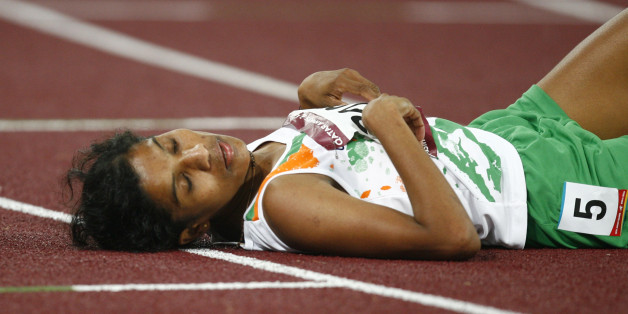 India's Jaisha Orchatteri Puthiya Veetil lies on the track after the women's 5000m final at the 15th Asian Games in Doha December 11, 2006. Veetil took the bronze medal.   REUTERS/Jerry Lampen  (QATAR)