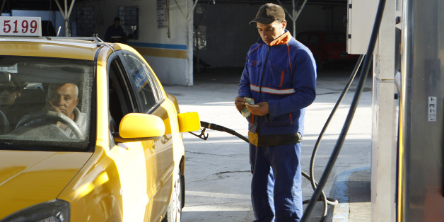 An employee counts money as he fills up a taxi's tank with fuel at a gas station in Tunis March 11, 2013. Protests and strikes planned in Tunisia over the next few weeks will test the government's ability to repair its shaky finances - and may affect its efforts to secure a $1.78 billion loan from the International Monetary Fund. Last week authorities raised most fuel prices for the second time in six months, lifting petrol prices at the pump by 6.8 percent. Taxes on alcohol increased this month, and several weeks ago the state-controlled milk price rose. Picture taken March 11, 2013. To match Mideast Money TUNISIA-SUBSIDIES/    REUTERS/Zoubeir Souissi  (TUNISIA - Tags: BUSINESS POLITICS ENERGY)