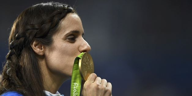 2016 Rio Olympics - Athletics - Victory Ceremony - Women's Pole Vault Victory Ceremony - Olympic Stadium - Rio de Janeiro, Brazil - 20/08/2016. Ekaterini Stefanidi (GRE) of Greece kisses her gold medal. REUTERS/Dylan Martinez  FOR EDITORIAL USE ONLY. NOT FOR SALE FOR MARKETING OR ADVERTISING CAMPAIGNS.