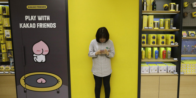 In the April 4, 2016, photo, Kim Do-hee, an employee of Kakao Friends Shop, uses a smartphone beside its goods in Seoul, South Korea. Kakao Talk and Line are two Asian mobile messengers that outgrew Facebook and Twitter in Japan and in South Korea in terms of user number. But as growth pace of users and revenues slowed, they have come under pressure to monetize new services. (AP Photo/Ahn Young-joon)