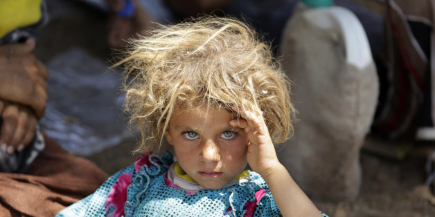 A girl from the minority Yazidi sect, fleeing the violence in the Iraqi town of Sinjar, rests at the Iraqi-Syrian border crossing in Fishkhabour, Dohuk province August 13, 2014. REUTERS/Youssef Boudlal (IRAQ - Tags: CIVIL UNREST POLITICS TPX IMAGES OF THE DAY)