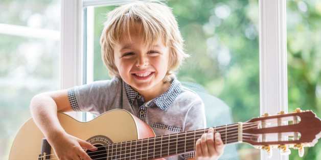 Happy smiling boy learning to play the acoustic guitar