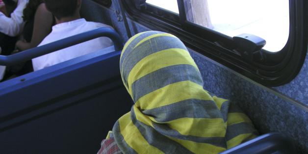 Eine Frau mit Kopftuch sitzt im Bus