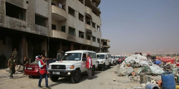 Des ambulances du Croissant rouge escortés par des soldats de l'armée syrienne dans la ville rebelle de Daraya, le 26 août 2016