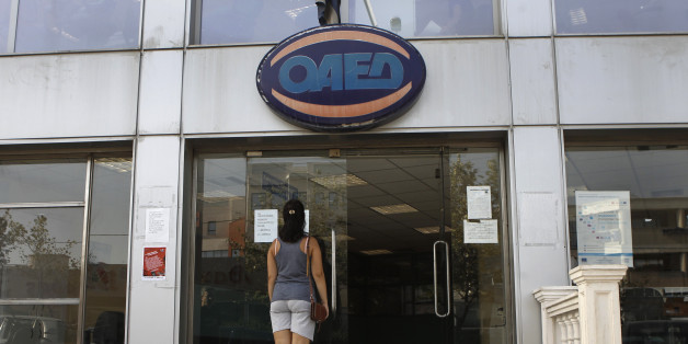A woman stands outside a Greek Manpower Employment Organisation (OAED) office in a northern suburb of Athens September 12, 2013. Greece's jobless rate rose to 27.9 percent in June from 27.6 percent in May, reflecting the impact of a six-year, austerity-fuelled recession, the country's statistics service ELSTAT said on Thursday. REUTERS/John Kolesidis (GREECE - Tags: POLITICS BUSINESS EMPLOYMENT)