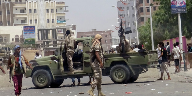 Soldiers and people gather at the site of an attack by a suicide bomber who drove a car laden with explosives into a compound run by local militias in the southern port city of Aden, Yemen August 29, 2016. REUTERS/Fawaz Salman