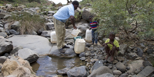 A man and his grandchildren collect water from the Nkuzana River as water to homes has been cut off due to drought near Pongola, northeast of Durban, January 20, 2016. REUTERS/Rogan Ward