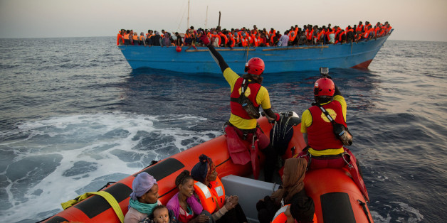 Helfer nähern sich im Mittelmeer eine Flüchtlungsboot aus Libyen