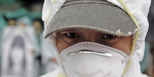 In this photo taken on March 25, 2010, a South Korean activist, wearing protective clothing, participates during a rally near the Samsung semiconductor factory in Yongin, south of Seoul, South Korea. Samsung Electronics said Thursday, April 15, 2010, workers at its semiconductor factories face no heightened cancer risk as the world's top maker of memory chips tried to quell health fears following employee illnesses and deaths. (AP Photo/ Lee Jin-man)