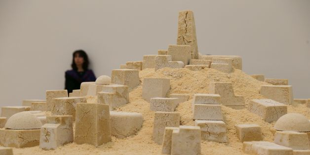 A visitor stands in front of the artwork 'Untitled' (Gharda'a), by Kader Attia, an Algerian city made out of crumbling couscous, in the new Switch House extension of the Tate Modern in London on  June 14, 2016.  / AFP / Daniel Leal-Olivas / RESTRICTED TO EDITORIAL USE - MANDATORY MENTION OF THE ARTIST UPON PUBLICATION - TO ILLUSTRATE THE EVENT AS SPECIFIED IN THE CAPTION        (Photo credit should read DANIEL LEAL-OLIVAS/AFP/Getty Images)