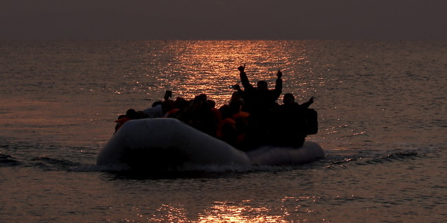 Refugees and migrants wave as they approach the shores of the Greek island of Lesbos on a dinghy during sunrise, March 20, 2016. REUTERS/Alkis Konstantinidis
