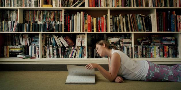 Young woman lying on floor by book shelves, reading, side view