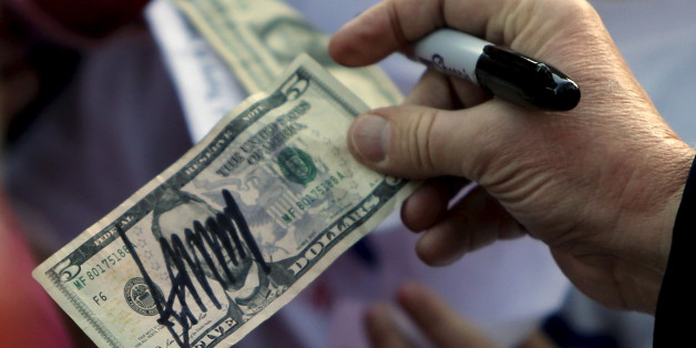 U.S. Republican presidential candidate Donald Trump hands a five-dollar bill back to a supporter after signing it for her following a rally with sportsmen in Walterboro, South Carolina February 17, 2016. REUTERS/Jonathan Ernst