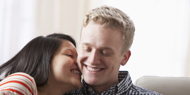 Smiling couple hugging on sofa