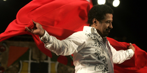 Algerian singer Cheb Khaled covers himself with a Moroccan flag during his concert at the annual Gnaoua Music Festival in Essaouira  June 28, 2009. The festival features a mixture of traditional Moroccan and world music, and dancers sometimes go into a trance. REUTERS/Rafael Marchante (MOROCCO SOCIETY ENTERTAINMENT)
