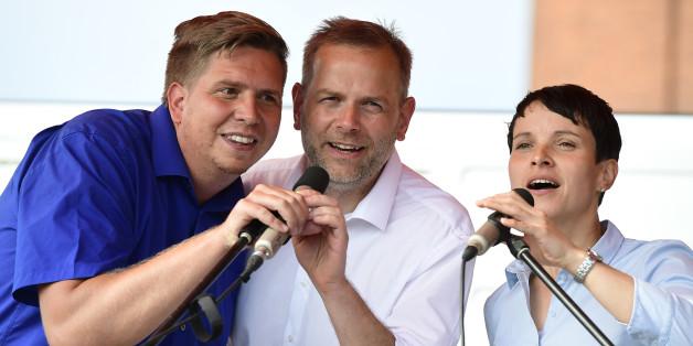 Leif-Erik Holm, Frauke Petry (r) und Lars Loewe (l) singen auf einer Veranstaltung in Wismar die Nationalhymne