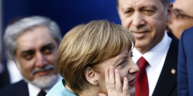 German Chancellor Angela Merkel (C) reacts next to Afghanistan's Chief Executive Abdullah Abdullah (L) and Turkey's President Tayyip Erdogan as they observe a fly past during the NATO Summit in Warsaw, Poland July 8, 2016.     REUTERS/Kacper Pempel