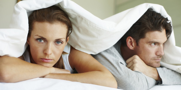Portrait of an angry woman and her frustrated boyfriend lying beneath the bed covers