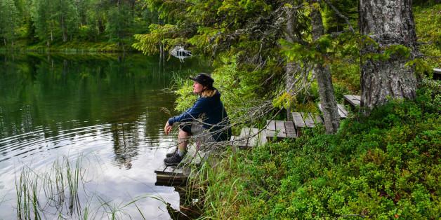 Woman sitting on pier on mountain lake