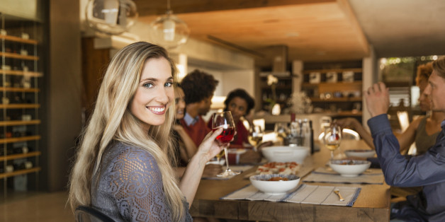 Smiling woman holding a glass at a table having dinner with friends.