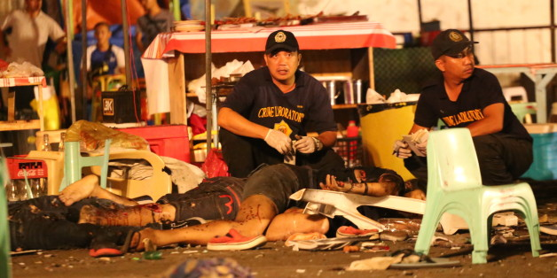 Philippine police investigators check bodies at a blast site at a night market that has left at least several people dead and wounded others in southern Davao city, Philippines late Friday Sept. 2, 2016. The powerful explosion at a night market late Friday in Philippine President Rodrigo Duterte's hometown in the southern Philippines took place amid a security alert due to a major offensive against Abu Sayyaf militants in the region, officials said. (AP Photo/Manman Dejeto)