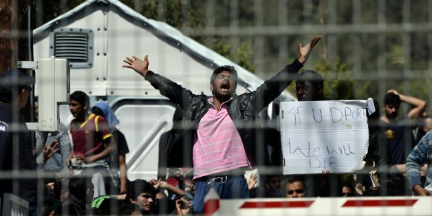 Pakistani and Afghan migrants protest inside the Moria detention center against the deportation to Turkey, in Mytilene on April 5, 2016. Migrants return from Greece to Turkey begun on April 4 under the terms of an EU deal that has worried aid groups, as Athens struggles to manage the overload of desperate people on its soil. Over 51,000 refugees and migrants seeking to reach northern Europe are stuck in Greece, after Balkan states sealed their borders. Hundreds more continue to land on the Greek