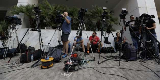 TV crews work outside the Greek Secretariat General for Media and Communication in Athens on Wednesday, Aug. 31, 2016 where eight bidders are taking part for second day in the process that would see eliminated TV stations close by the end of the year. Greece's left-wing government launched an auction Tuesday for four private national television licenses, reducing the number from seven after a heated public debate on corruption in the financially troubled country. (AP Photo/Thanassis Stavrakis)