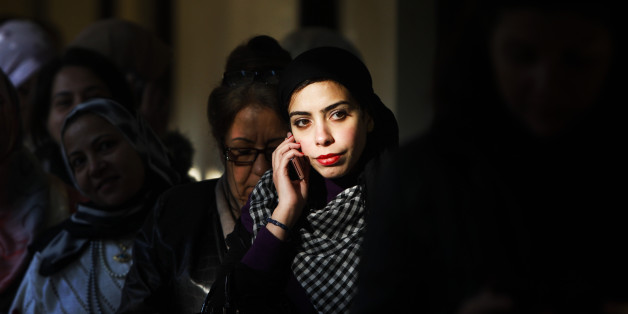 An Egyptian woman talks on her mobile phone while waiting to to vote in Maadi, a suburb of Cairo, Egypt, Monday, Nov. 28, 2011. Voting began on Monday in Egypt's first parliamentary elections since longtime authoritarian leader Hosni Mubarak was ousted in a popular uprising nine months ago. The vote is a milestone many Egyptians hope will usher in a democratic age after decades of dictatorship. (AP Photo/Tara Todras-Whitehill)