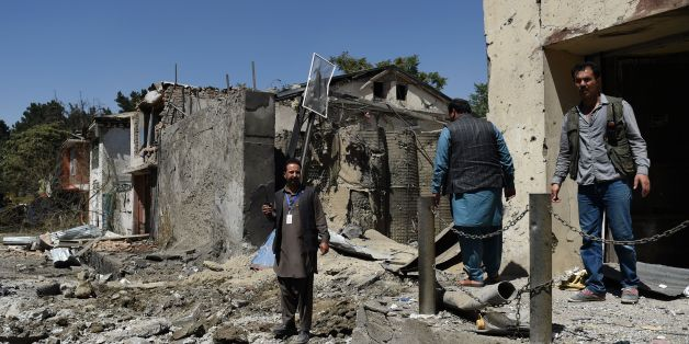 Afghan security personnel and residents walk at the site of a car bomb blast that targeted the CARE International compound at Shar-e-Naw in Kabul on September 6, 2016.Explosions rang out during an hours-long attack on an international charity in Kabul, the latest assault in a wave of violence in the Afghan capital that has killed at least 24 people and wounded dozens. / AFP / WAKIL KOHSAR        (Photo credit should read WAKIL KOHSAR/AFP/Getty Images)