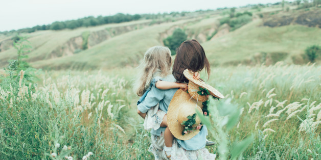 The back view of young mother and daughter on green grass background.