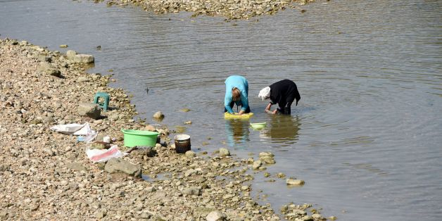 Tunisian women wash wool in the Medjerda River (also written Majerda), whose water level is low due to low rainfall, on August 21, 2016 in the small town of Testour, located in the north of Tunisia in the Beja province. / AFP / FETHI BELAID        (Photo credit should read FETHI BELAID/AFP/Getty Images)