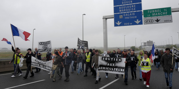 "People block the highway leading to Calais and the Channel tunnel in Calais, northern France, Monday, Sept. 5, 2016. Hundreds of truckers in big rigs, farmers in tractors and dockers and merchants on foot blocked a major highway in northern France on Monday to demand the closure of the Calais migrant camp known as the ""jungle."" (AP Photo/Michel Spingler)"