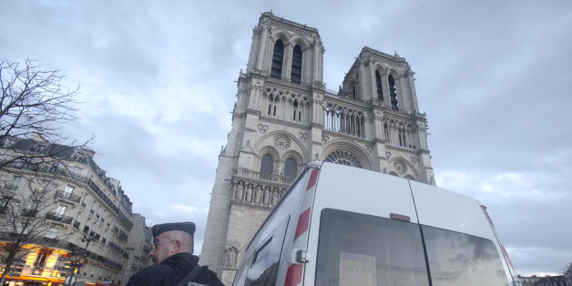 "A French Police stand in front of Notre Dame cathedral, in Paris, Thursday, Dec. 25, 2015. France's interior minister Bernard Cazeneuve announced Tuesday that churches will keep only one door open, instead of multiple doors, ""to have better filtering at the entrance."" (AP Photo/Jacques Brinon)"