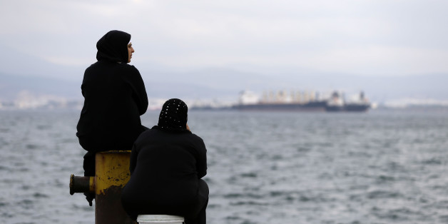 Two women sit on a dock of a refugee camp which houses about 3,200 refugees and migrants, in the western Athens' suburb of Skaramagas, Thursday, Aug. 25, 2016. Numbers arriving in Greece have dropped dramatically since the March agreement with Turkey, but over 58,000 people remain stranded in the country, most in army-built camps on the mainland and over 9,000 refugees are receiving hotel vouchers or live in vacant apartments. (AP Photo/Thanassis Stavrakis)