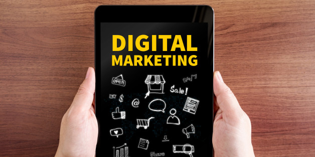 Two hand holding tablet with Digital marketing and doodle icon on screen at dark brown table top,Digital business concept.