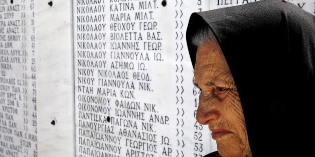 Survivor Loukia Gavrili, 86,  sits by a plaque featuring the names of those killed by Nazi troops, on the day of the 71st  anniversary of the Nazi wartime Distomo massacre, in the village of Distomo, in central Greece, June 10, 2015.  On June 10, 1944, during the German occupation of Greece in World War Two, Waffen-SS troops of the 4th SS Polizei Panzergrenadier Division under the command of Fritz Lautenbach, burned the village of Distomo to the ground and killed 218 civilians, including women and children, in retaliation for an attack by partisans. Athens's demands for 278.7 billion Euros in reparations from Germany have gained momentum in recent years as Greeks suffer hardship during the economic crisis but while Berlin has repeatedly rejected the claims, some, including German President Joachim Gauck, have expressed their support  Gavrili lost her sister and mother in the massacre.  REUTERS/Yannis Behrakis      TPX IMAGES OF THE DAY