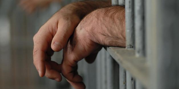 man behind bars or in jail