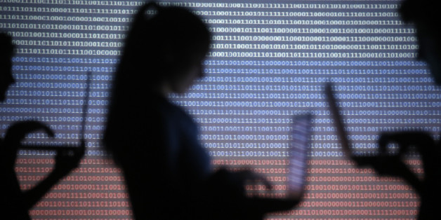 People are silhouetted as they pose with laptops in front of a screen projected with binary code and a Russian national flag, in this picture illustration taken in Zenica October 29, 2014.    REUTERS/Dado Ruvic (BOSNIA AND HERZEGOVINA  - Tags: SCIENCE TECHNOLOGY)
