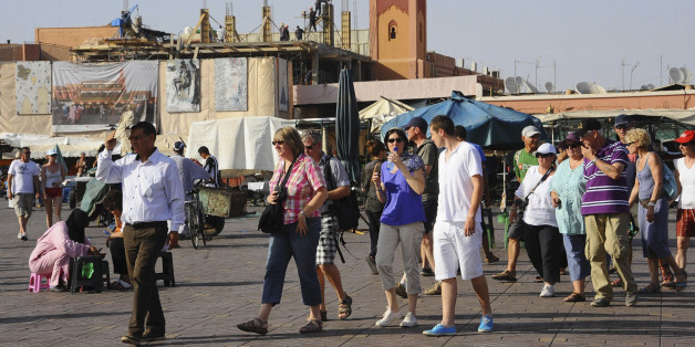 Tourists walk around the Argana restaurant (background) at Marrakesh?s famous Jemma el-Fnaa square, June 22, 2012. An Islamist bombing of a cafe last year hurt trade for the snake charmers and trinket sellers who entice foreign tourists to the Jamaa el-Fna square, but the euro zone debt crisis risks doing far more lasting damage to business. Tourists from western Europe typically account for more than 70 percent of all visitors annually to Morocco, where total visitor numbers fell 10 percent in