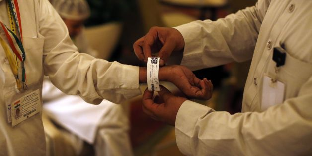 A Saudi official adjusts an electronic bracelet that Saudi authorities are giving to pilgrims ahead of the annual Hajj Muslim pilgrimage in the holy city of Mecca on September 8, 2016. Close to 1.5 million Muslims from around the world had descended on Saudi Arabia for the annual hajj pilgrimage, undeterred by last year's stampede disaster but with Iranians absent. / AFP / AHMAD GHARABLI        (Photo credit should read AHMAD GHARABLI/AFP/Getty Images)
